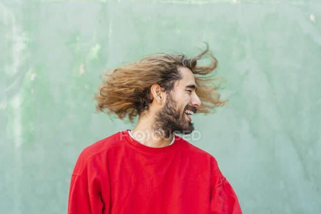 Одягнений молодий чоловік з піднесенням волосся перед зеленою стіною. — стокове фото