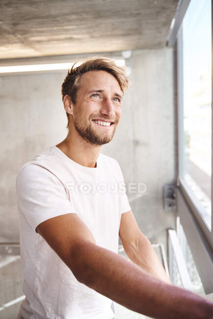 Portrait of smiling young man wearing white t-shirt looking out of window — Stock Photo