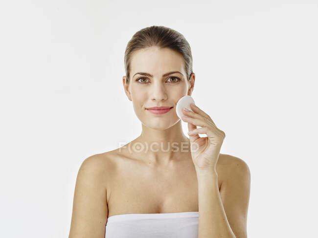 Retrato de mujer sonriente limpiando la cara con algodón - foto de stock