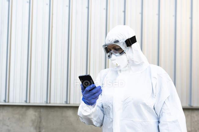 Científica con traje protector y máscara y mirando el smartphone - foto de stock