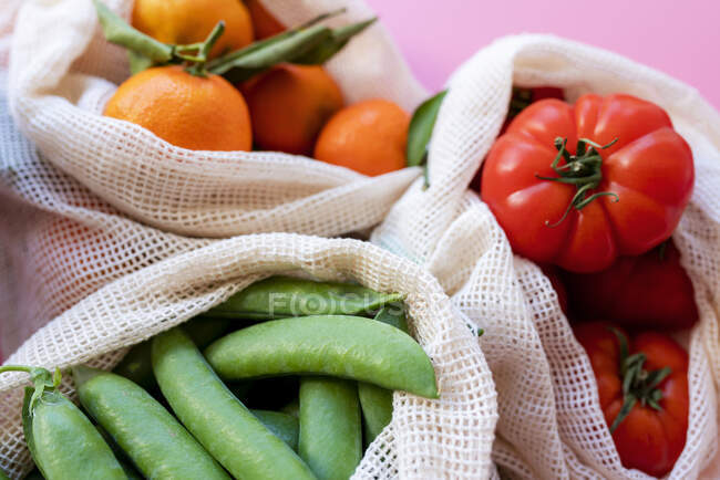 Bolsas de malla reutilizables ecológicas con guisantes verdes frescos, tomates y clementinas - foto de stock