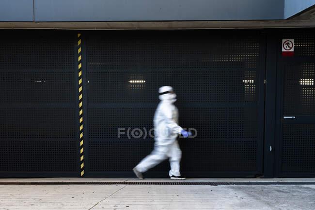 Cientista feminina vestindo roupa protetora e máscara e andando na frente de uma parede — Fotografia de Stock