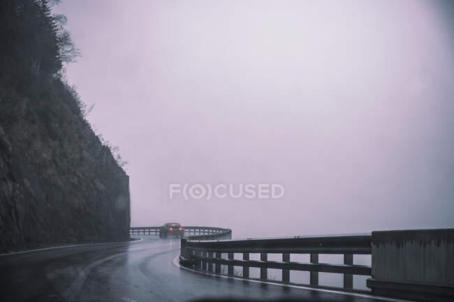 Italy, South Tyrol, Bolzano, Winding highway in rain and fog — Stock Photo