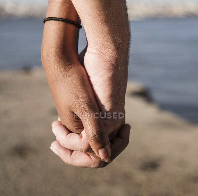 Close-up of couple holding hands at the waterfront — Stock Photo