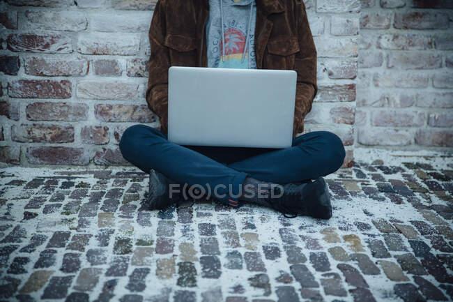 Adolescente usando portátil y sentado en un piso de piedra en la ciudad - foto de stock