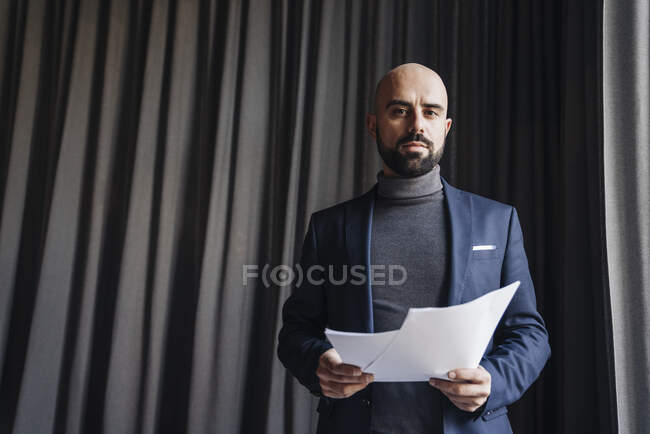 Businessman working in a cafe, holding documents — Stock Photo