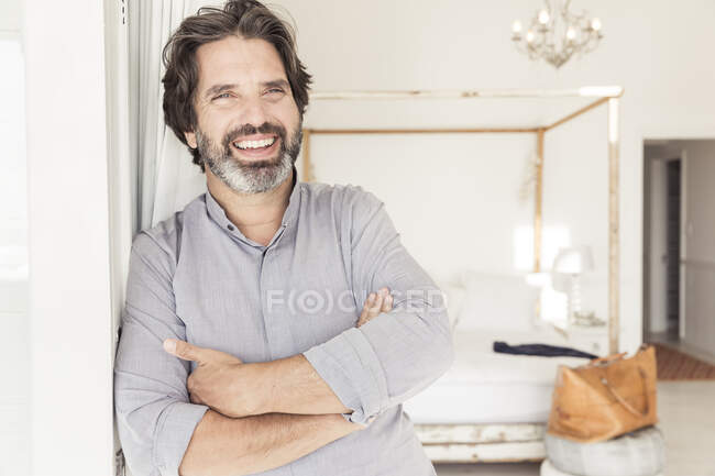Portrait of happy bearded man leaning against a wall — Stock Photo