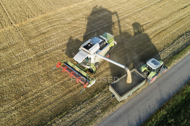 Germany, Bavaria, Drone view of combine harvester unloading grain on tractor — Stock Photo