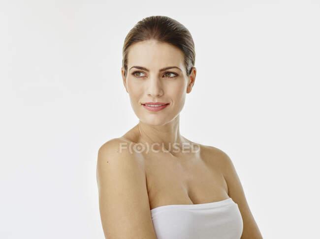 Retrato de mujer sonriente fondo blanco mirando a la distancia - foto de stock