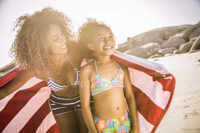 Felice madre e figlia con asciugamano sulla spiaggia — Foto stock