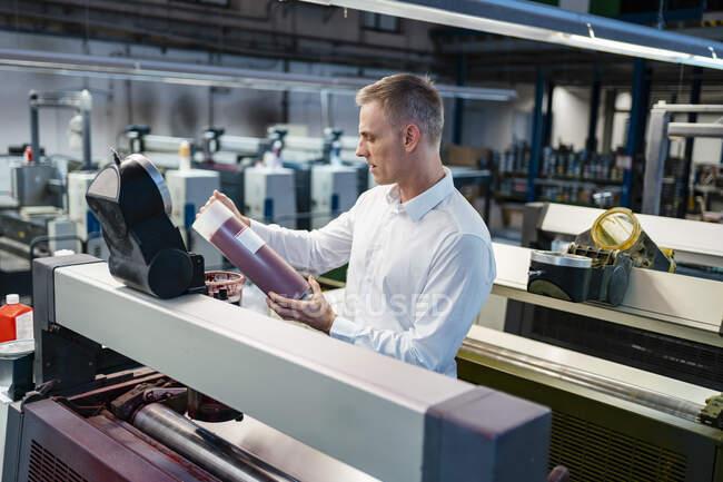 Чоловік у білій сорочці на фабриці, який оглядає продукт. — стокове фото