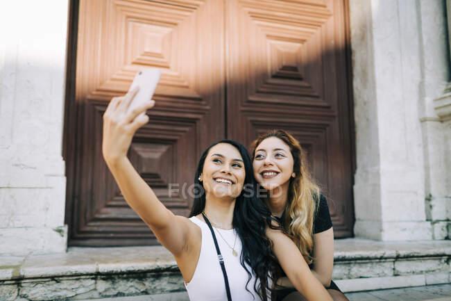 Retrato de dos jóvenes felices tomando selfie con smartphone, Lisboa, Portugal - foto de stock