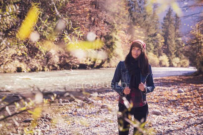 Donna con cappello di lana rossa e giacca di denim sul lungofiume — Foto stock