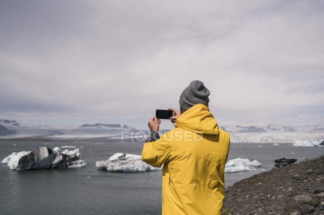 Mature man taking pictures of Vatnajokull glacier with binoculars, Iceland — Stock Photo