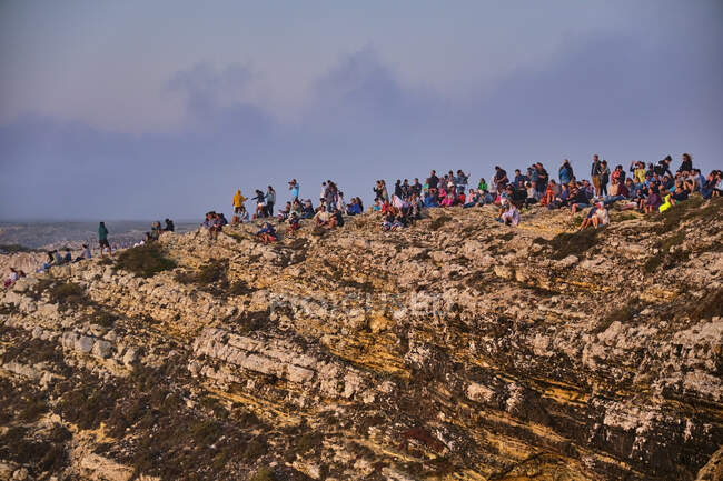Portugal, Algarve, Large group of people admiring sea from edge of cliff at Cape Saint Vincent — Stock Photo