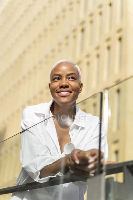 Atractiva empresaria apoyada en barandillas en la ciudad - foto de stock