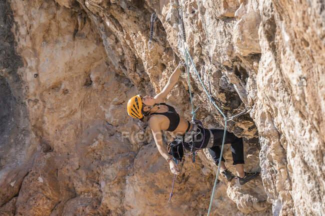 Donna arrampicata sulla parete rocciosa — Foto stock