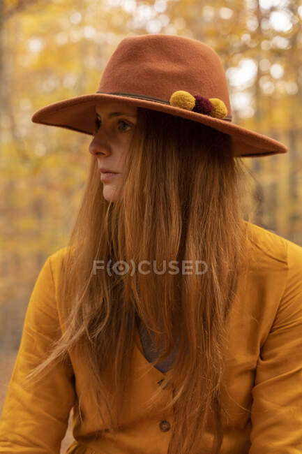 Portrait of fashionable redheaded young woman wearing felt hat in autumnal forest — Stock Photo