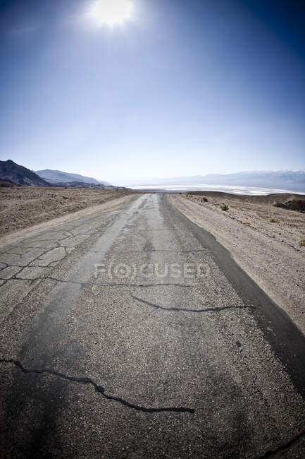 Etats-Unis, Californie, Le soleil brille sur une route fissurée dans la vallée de la mort — Photo de stock