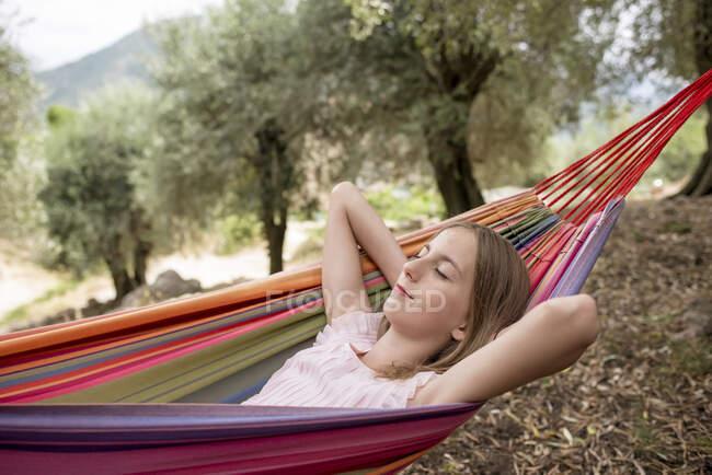 Girl resting in hammock in an olive grove — Stock Photo