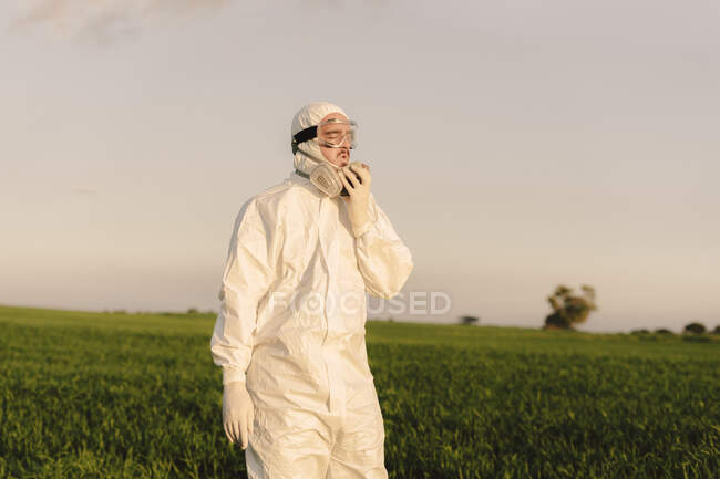 Hombre con traje protector en el campo quitándose el respirador - foto de stock