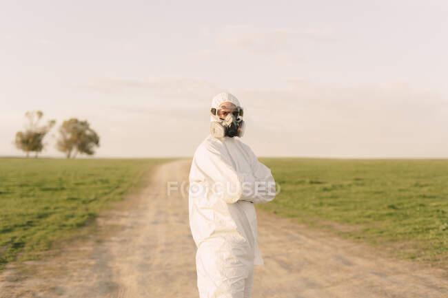 Retrato del hombre con traje protector y máscara de pie en la pista de tierra en el campo - foto de stock