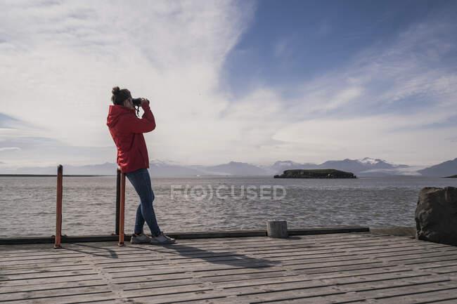 Молода жінка сидить на пристані і дивиться крізь бінокль (Південно - Східна Ісландія). — стокове фото