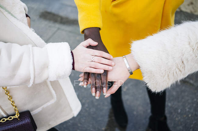 Close-up of three women stacking their hands — Stock Photo