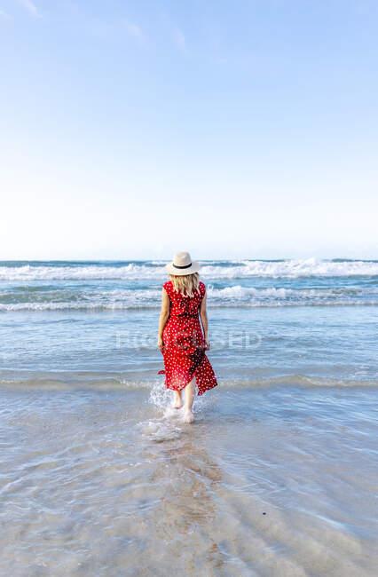 Vista posteriore della donna bionda che indossa vestito rosso e cappello e cammina in spiaggia in acqua — Foto stock
