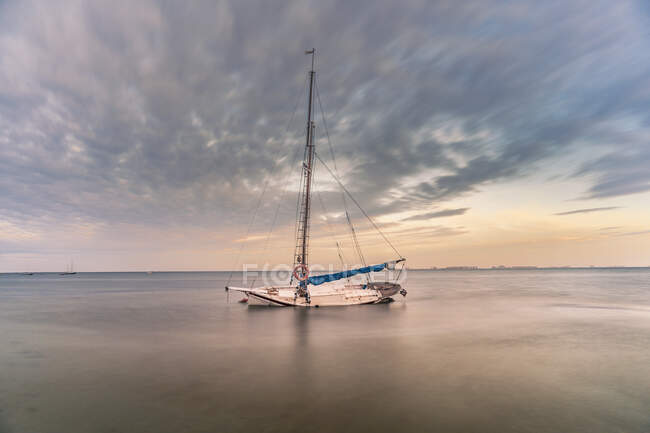 Spain, Murcia, Santiago de la Ribera, Abandoned sailboat on calm sea at sunset — Stock Photo
