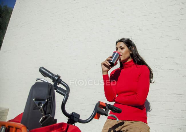 Молода жінка з велосипедом, схилившись на стіні, п