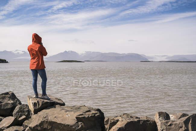 Молода жінка копає валуни, дивлячись на море, Південно - Східна Ісландія. — стокове фото