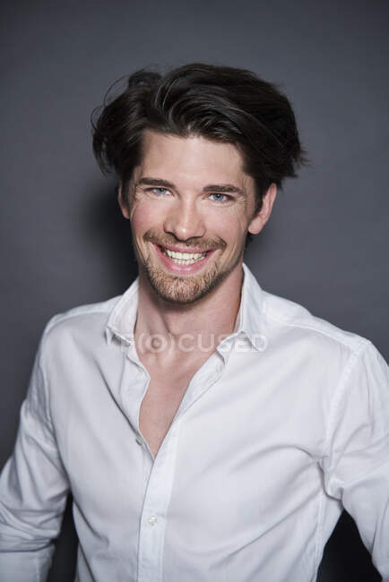 Portrait of smiling handsome man wearing white shirt — Stock Photo