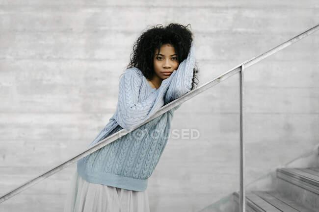 Hermosa joven mujer de pie en las escaleras al aire libre - foto de stock