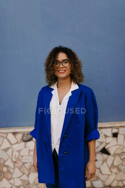 Portrait of smiling woman wearing glasses and blue blazer, blue wall in the background - foto de stock