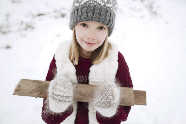 Portrait of smiling girl carrying firewood in winter — Stock Photo
