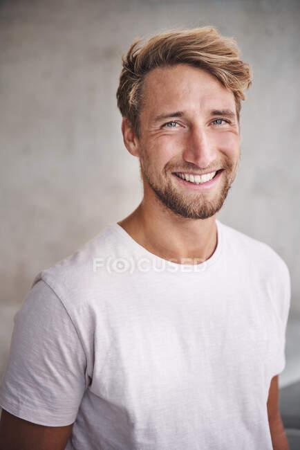 Porträt eines glücklichen jungen Mannes im weißen T-Shirt — Stockfoto