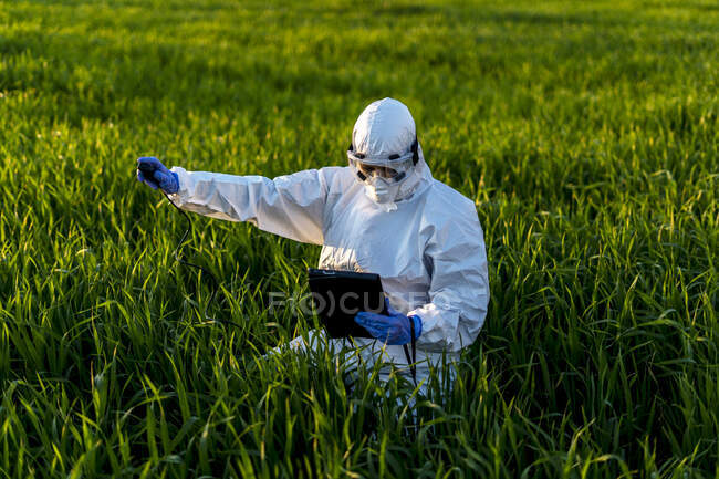 Female scientist researching in field and using measuring device — Stock Photo