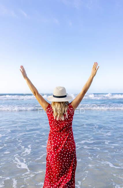 Donna bionda vestita di rosso e cappello e passeggiando lungo la spiaggia, Playa de Las Catedrales, Spagna — Foto stock
