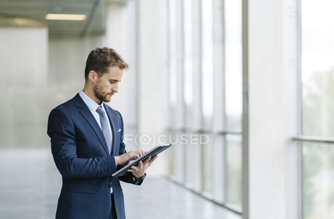 Businesman using tablet at the window — Stock Photo