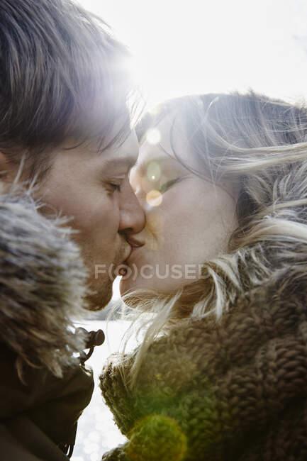 Цілування молодої пари в зимовий період. — стокове фото