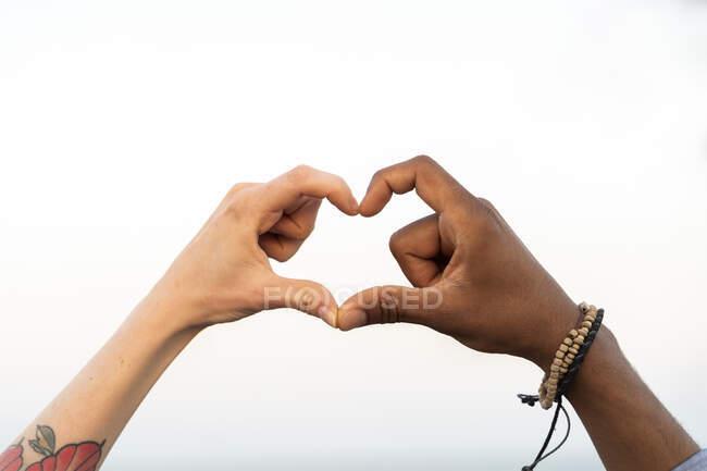 Primer plano de dos manos dando forma a un corazón - foto de stock