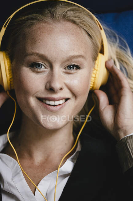Portrait of a smiling young businesswoman listening to music with headphones — Stock Photo