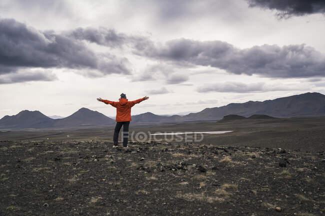 Молода жінка дивиться на нього з витягнутими руками, Хайленд, Ісландія. — стокове фото