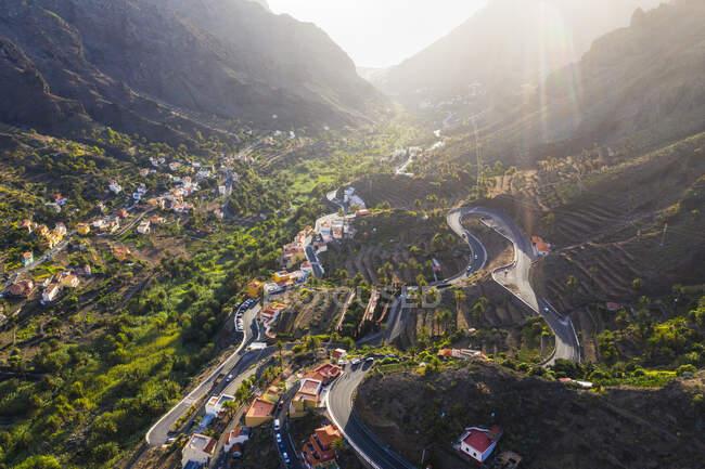 Spain, Canary Islands, La Gomera, Valle Gran Rey, El Retamal, Aerial view of towns and roads in mountain landscape — Stock Photo