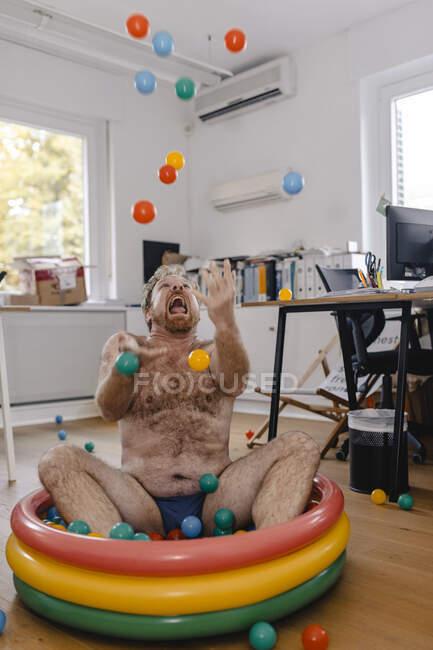 Loco hombre de negocios sentado en la piscina infantil en la oficina jugando con bolas - foto de stock