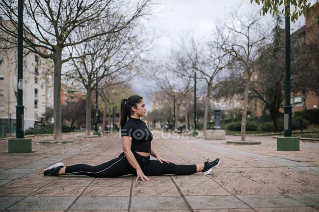 Молодая женщина в черной спортивной одежде делает шпагат на тротуаре — стоковое фото