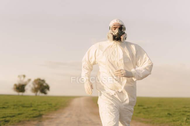 Hombre con traje protector y máscara corriendo por el campo - foto de stock