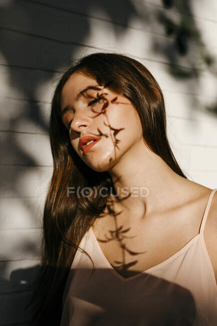 Portrait of teenage girl with shadow of leaves on her face — Foto stock