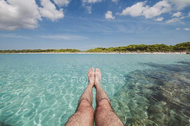 Gambe di un uomo di fronte alla spiaggia di Son Saura, Minorca, Spagna. — Foto stock